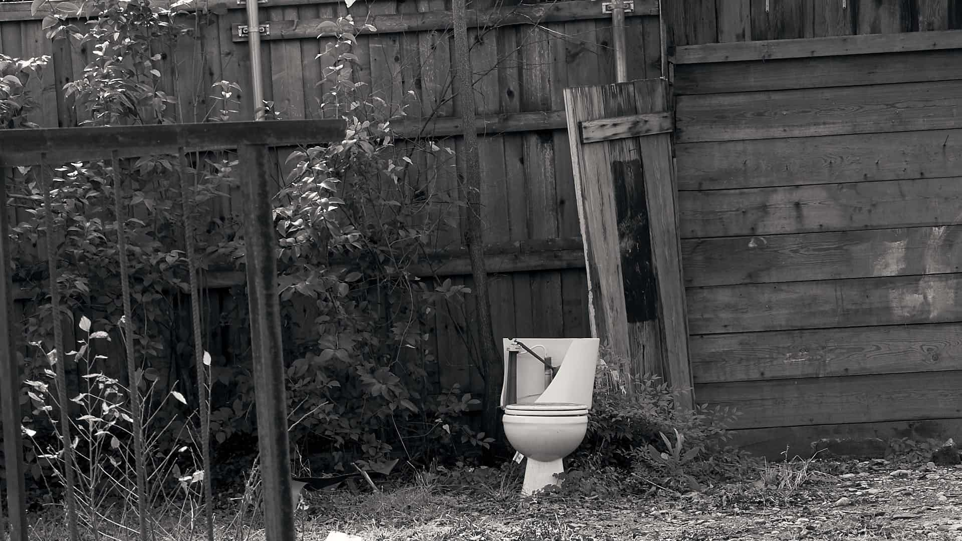 a toilet in the back yard of a house under renovation