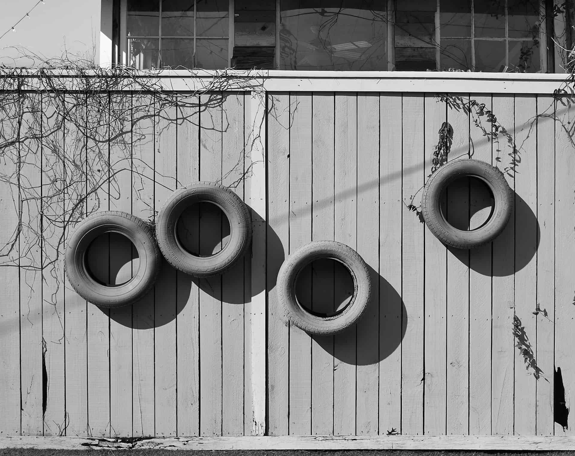 4 tires used as planters on a garden wall.