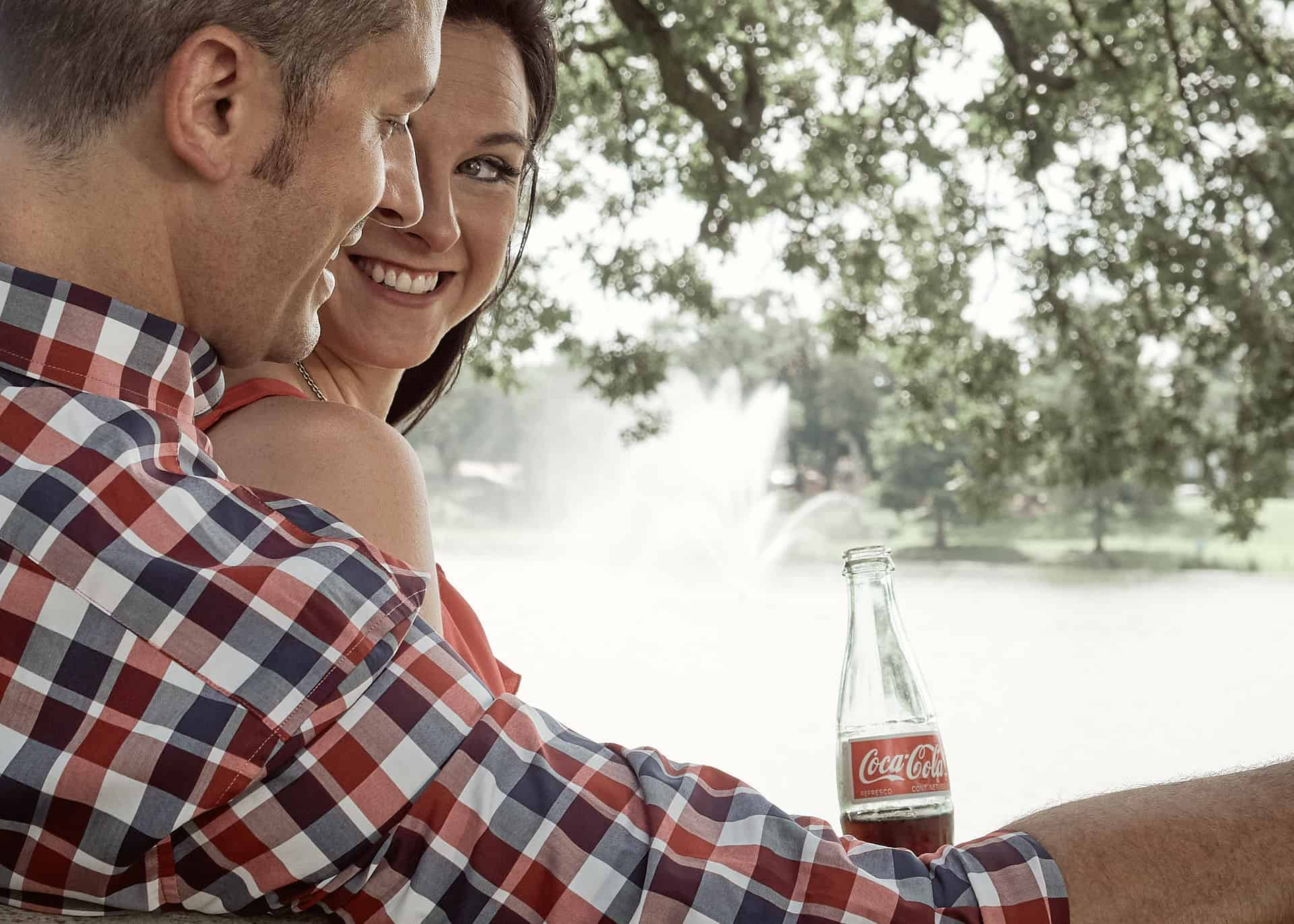 Couple in park drinking Coca-Cola.