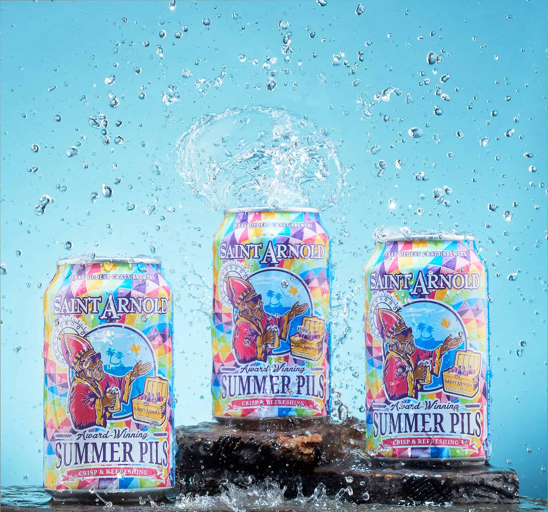 3 cans of Saint Arnold Beer splashed with water.