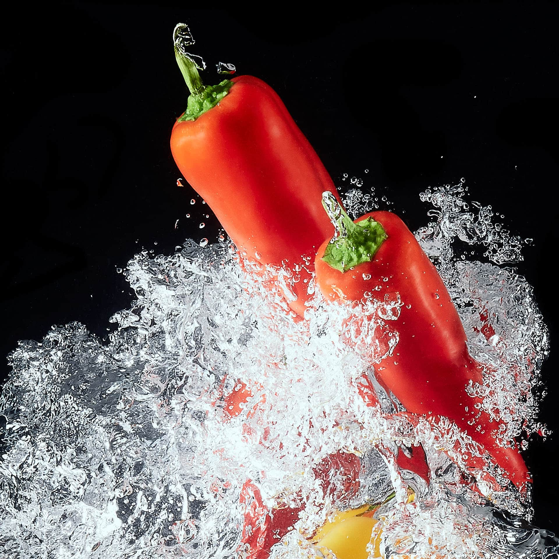 Closeup of sweet red peppers splashing in water on black background.