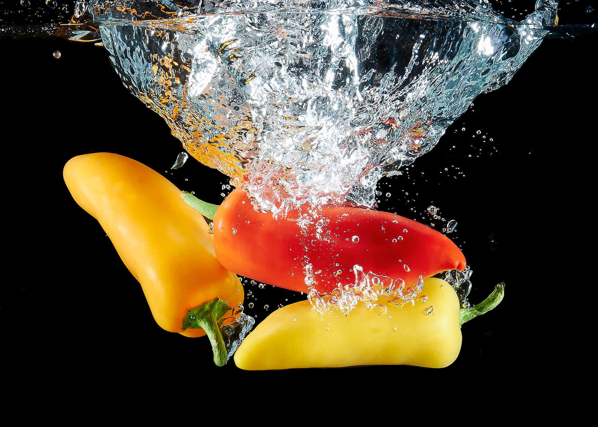 Sweet red, yellow and orange pepper splashed in water on black background.