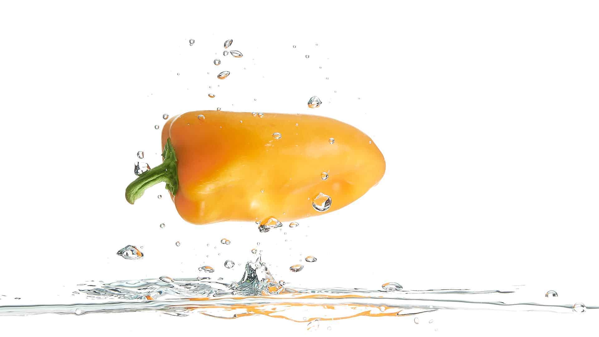Sweet yellow pepper flying above water on white background.