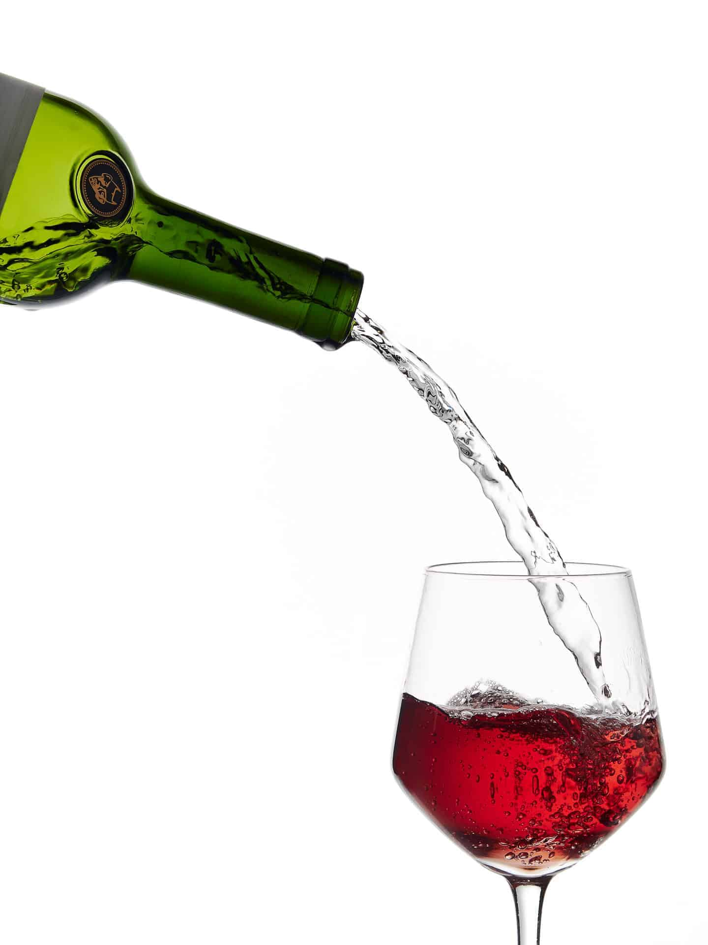 Water poured out of wine bottle into wine glass containing red wine.