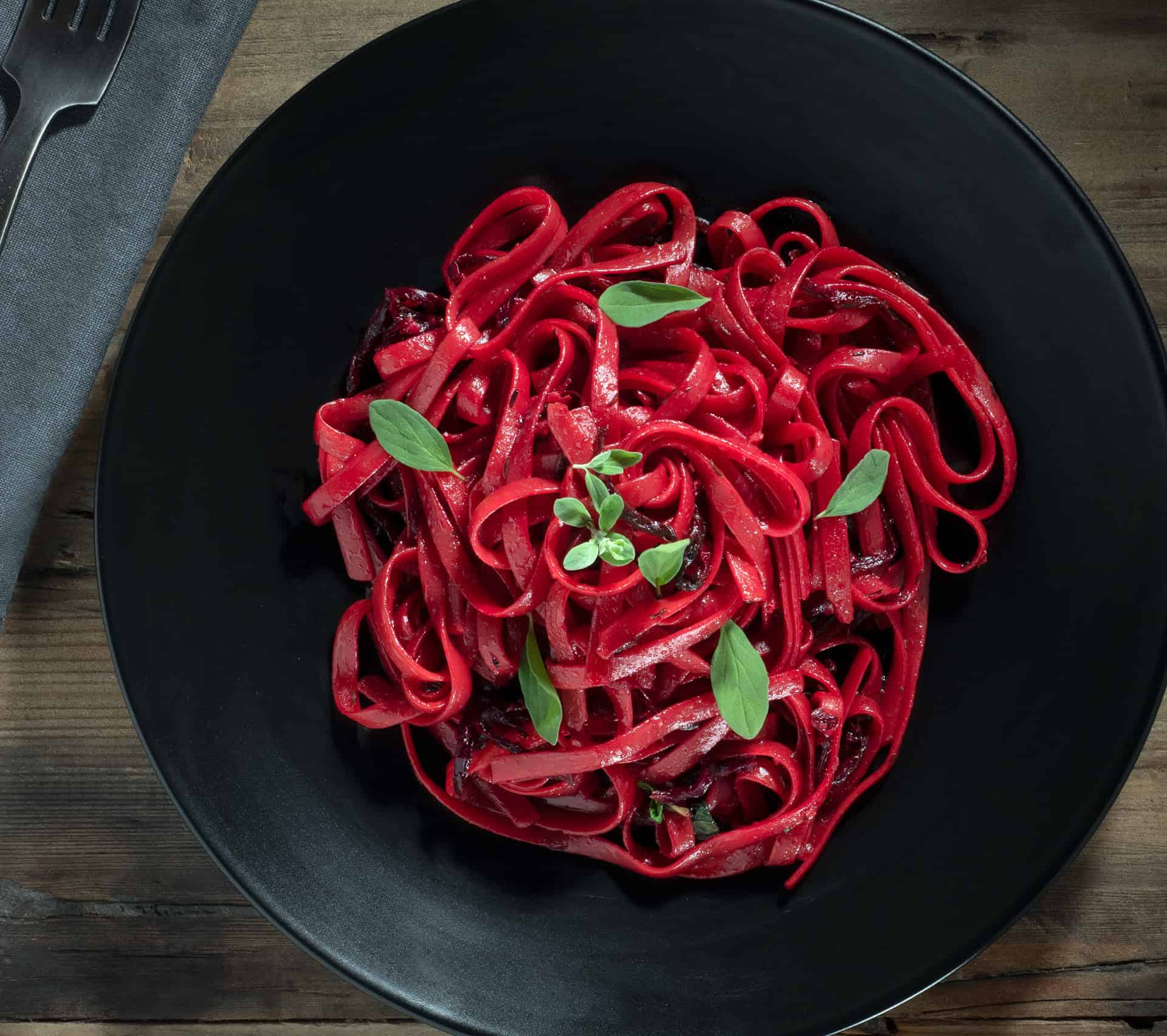 Red beet pasta on wood background.